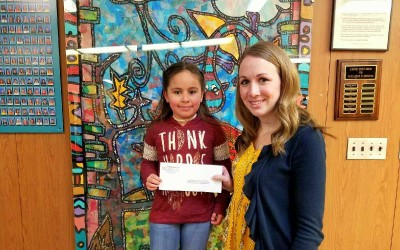 Teacher Heather Walters and student Julissa Cardel Torres pose holding a $50 check from BKS dental.