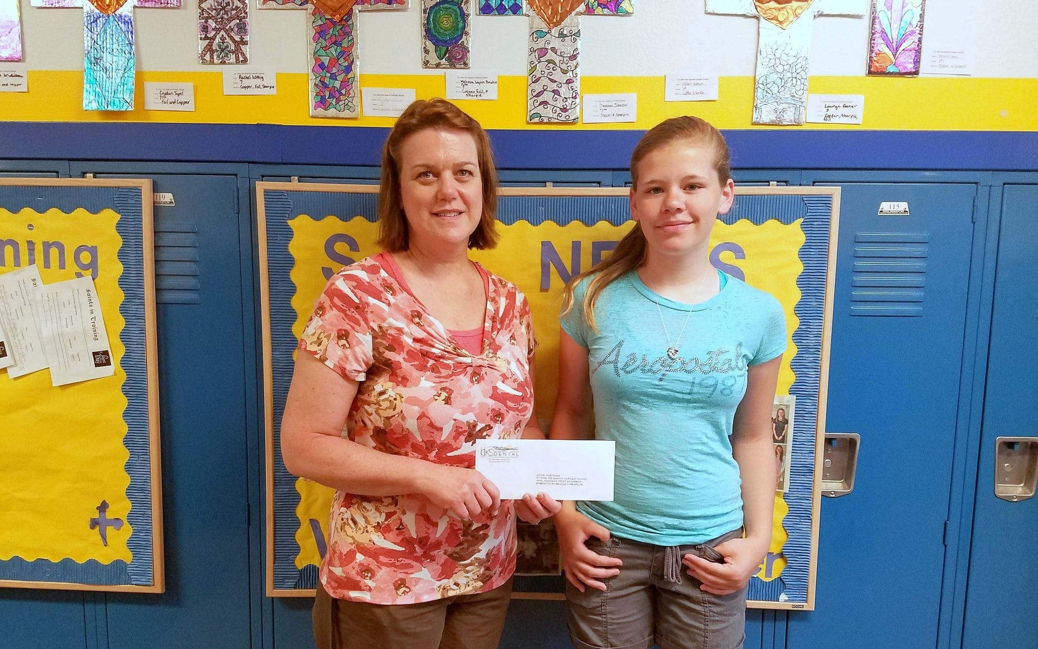 Recipient Jackie Haberman and nominating student Melissa Lyn Bruhn pose for picture holding check envelope.