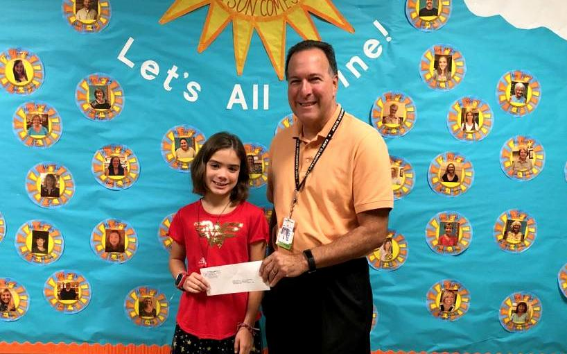 Teacher and student hold check in envelope smiling standing in front of a wall.