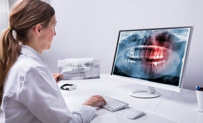 Female dentist looks over the xrays of a patient