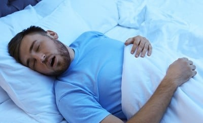 bearded man in blue shirt snores while laying in bed