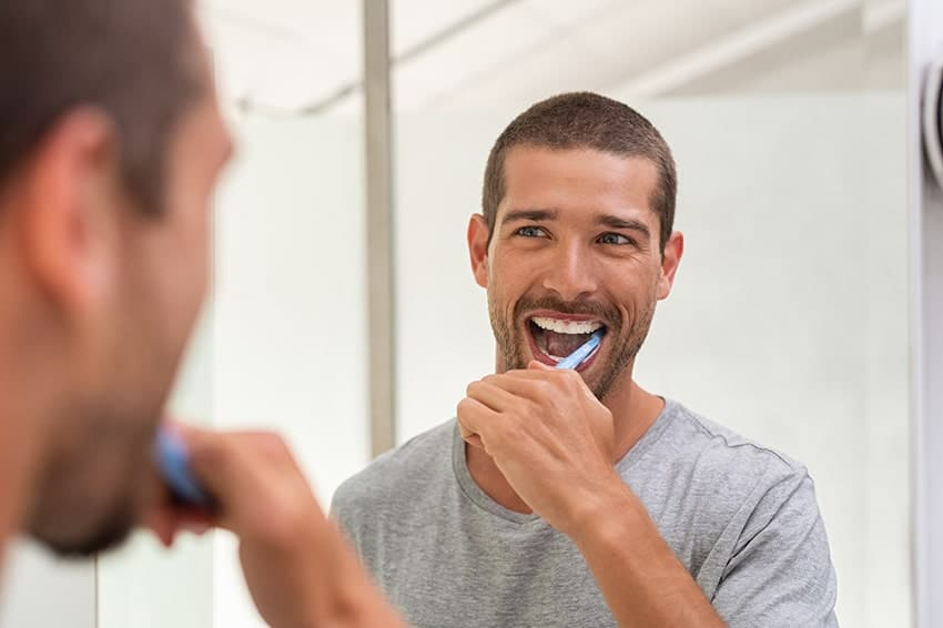 young man brushing his teeth in front of the bathroom mirror
