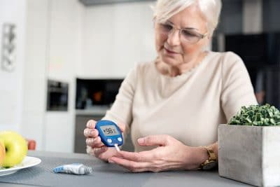 Older woman checks her blood sugar with a glucose meter