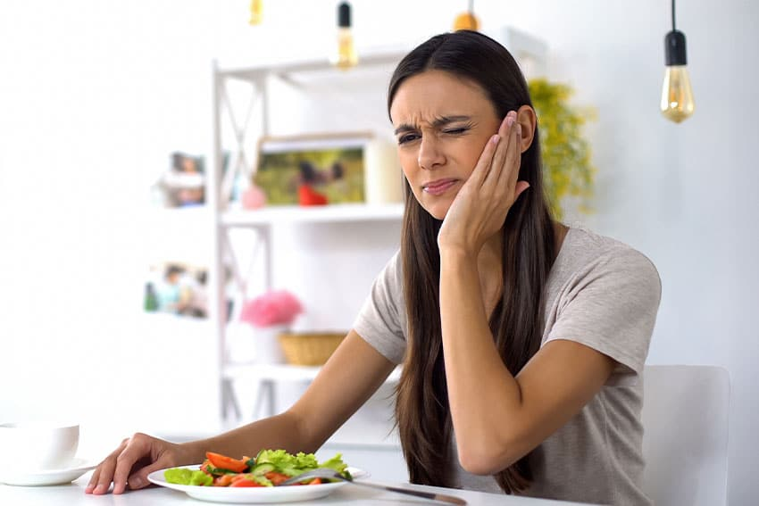 young woman holds her jaw due to pain while eating a salad for lunch