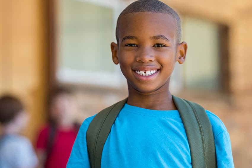 young boy standing outside school with backpack and a smile