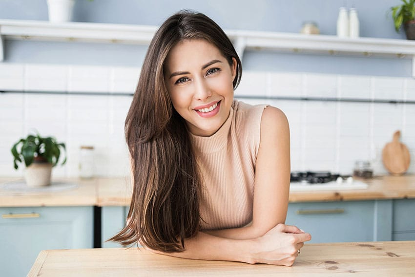 woman leaning on her countertop at home