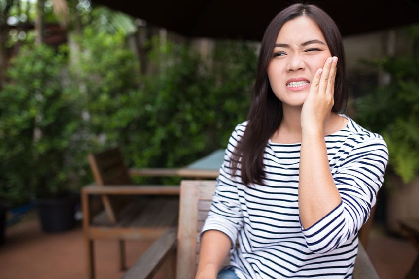 woman sits on her outdoor patio with a toothache